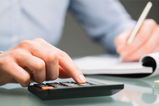 chartered accountant using a calculator to solve tax accounting issues